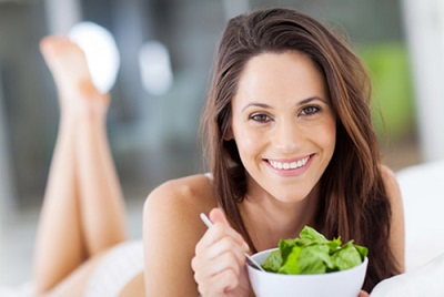 happy young woman eating green salad on bed